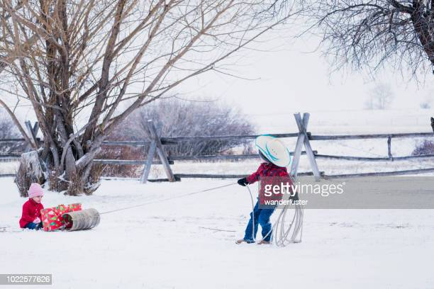 boy pulls sister on sled with christmas present in winter - cowboy christmas stock pictures, royalty-free photos & images