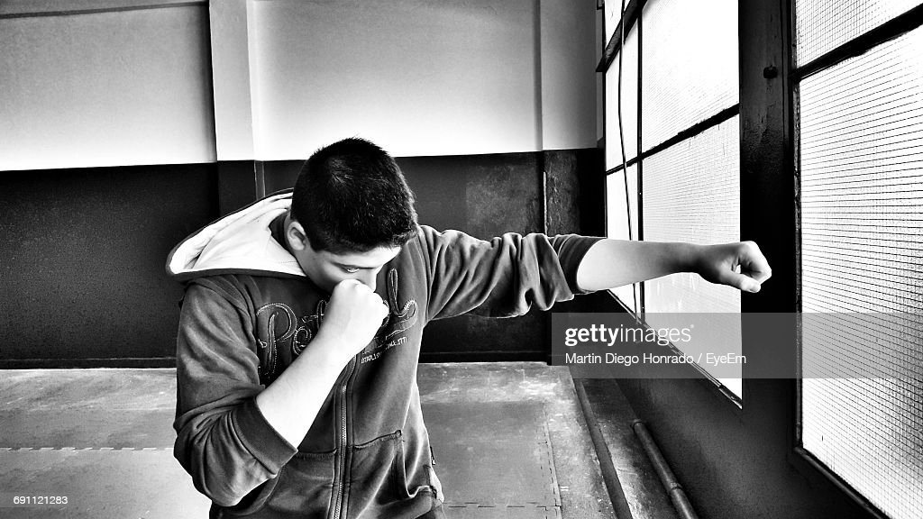 Boy Punching By Window In Room : Stock Photo