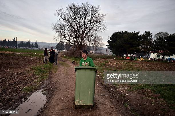 Boy pushes a garbage bin filled with firewood at the makeshift camp at the Greek-Macedonian borders, near the village of Idomeni, where thousands of...