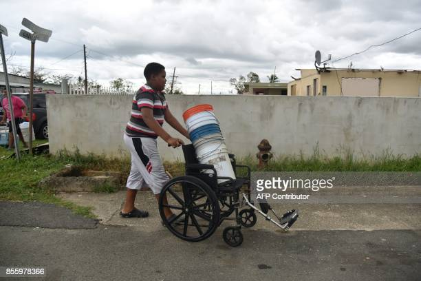 A boy pushes a wheelchair loaded with buckets to carry water in Vega Baja Puerto Rico on September 30 due to the lack of water after the passage of...