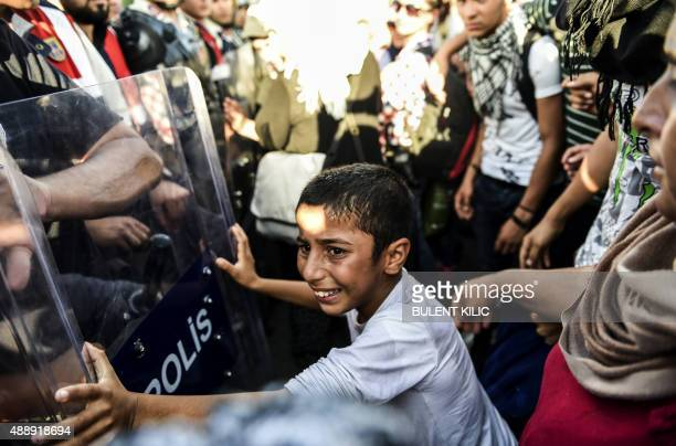 Boy pushes against a police barricade as Syrian refugees and migrants as they march along the highway towards the Turkish-Greek border at Edirne on...