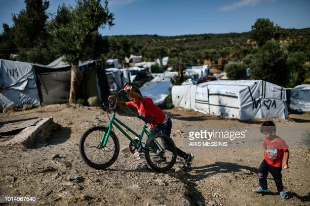 A boy pushes his bicycle at a camp next to the Moria refugee camp in the island of Lesbos on August 5 2018