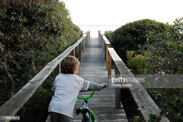 boy pushing bike down boardwalk - ヒルトンヘッド ストックフォトと画像