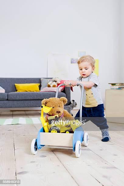 Boy pushing cart of toys at home