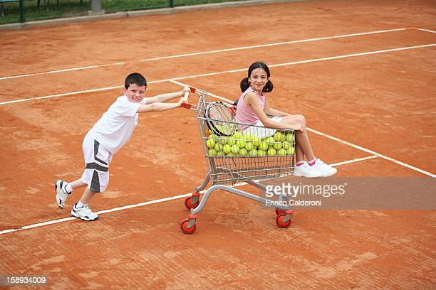 Boy Pushing Girl In Trolley With Full Of Tennis Balls