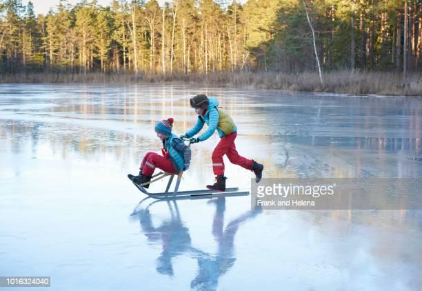 boy pushing his brother on sleigh across frozen lake - patinar fotografías e imágenes de stock