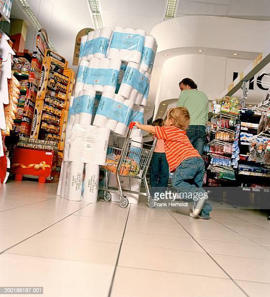 boy (2-4) pushing mini supermarket trolley into toilet roll display - ondeugendheid stockfoto's en -beelden