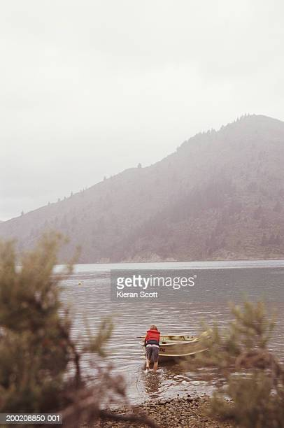Boy (7-9) pushing rowboat into bay, rear view