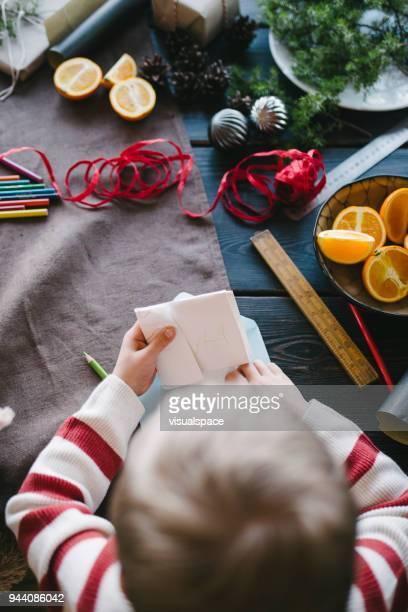 Boy puts a letter into envelope