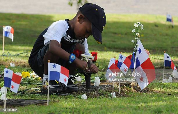 A boy puts flowers on the grave of a relative who died in the 1989 US invasion to Panama at the Jardin de la Paz cemetery in Panama City on December...