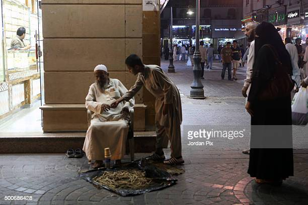 A boy puts some money in the hand of a blind old man vendor selling miswak at the popular market of Qabil street in the heart of Jeddah historic...