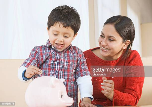 Boy putting a coin in a piggy bank with his mother sitting beside him