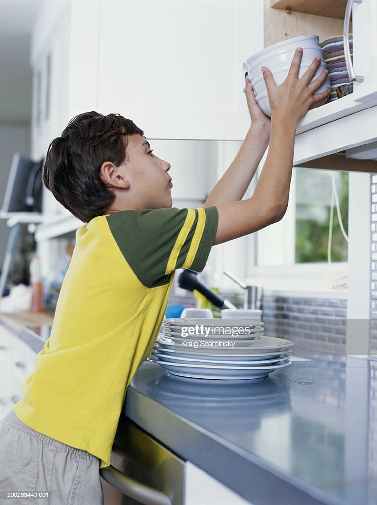 Boy (6-8) putting bowls away in kitchen cupboard, side view : Stock Photo