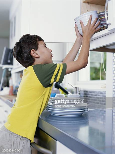 Boy (6-8) putting bowls away in kitchen cupboard, side view