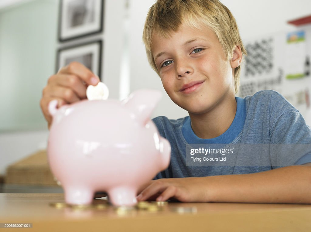 Boy (7-9) putting coin into piggy bank, smiling, portrait : Stock Photo