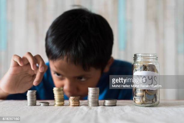 Boy Putting Coins In Jar On Table