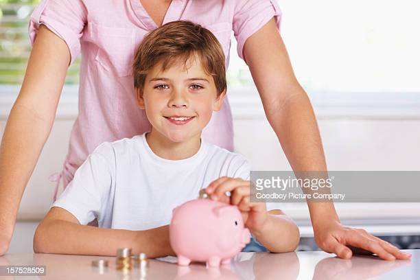 Boy putting coins in piggy bank with mother behind him