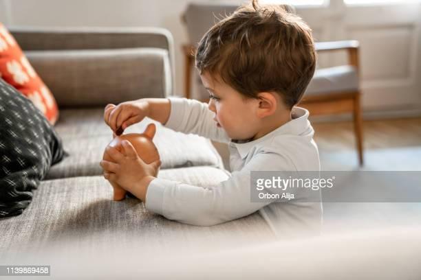 boy putting coins on piggy bank - economia imagens e fotografias de stock