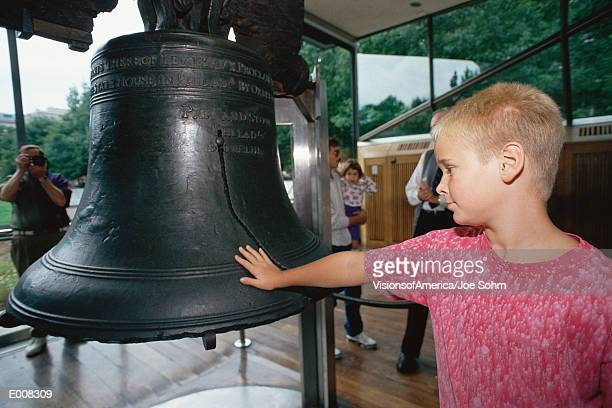 boy putting his hand on liberty bell - liberty bell stock pictures, royalty-free photos & images