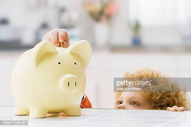 Boy (4-5) putting money in piggy bank, close-up