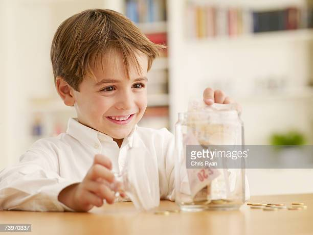 Boy putting money into a cookie jar