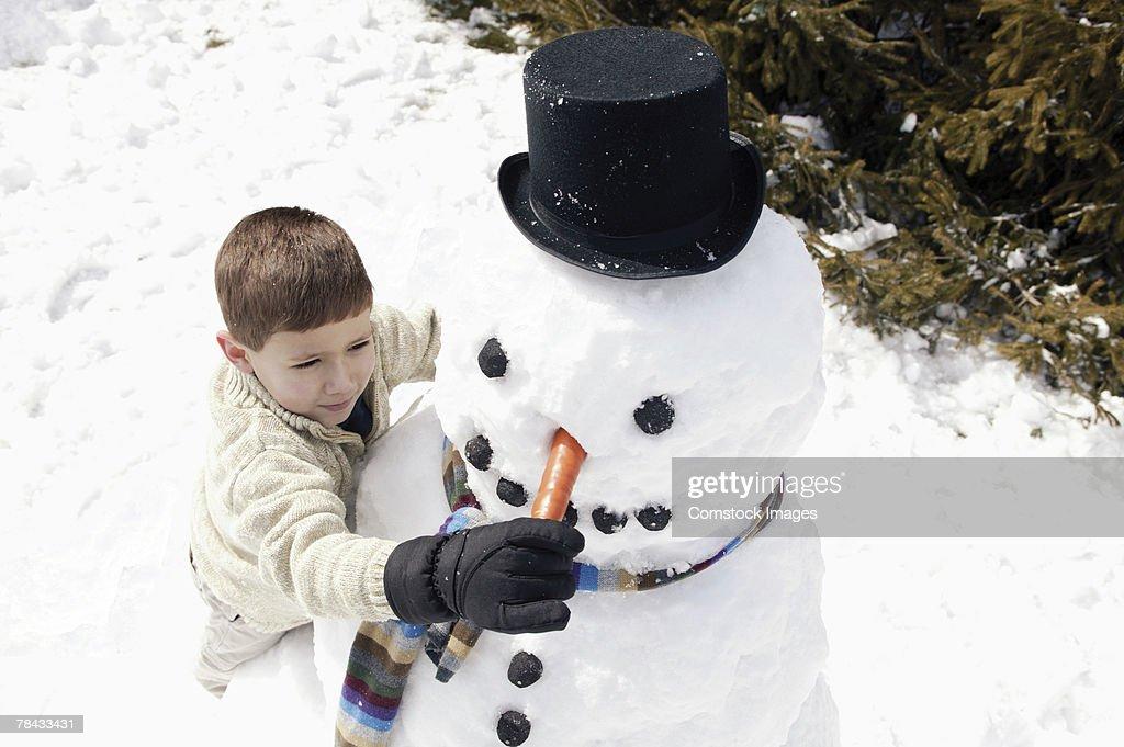 Boy putting nose on snowman : Stockfoto