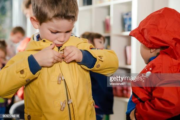 Boy putting on his raincoat in kindergarten