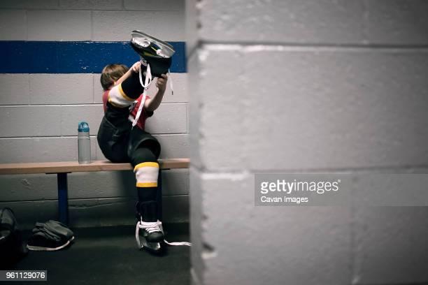 boy putting on ice hockey skates - ice hockey uniform stock pictures, royalty-free photos & images