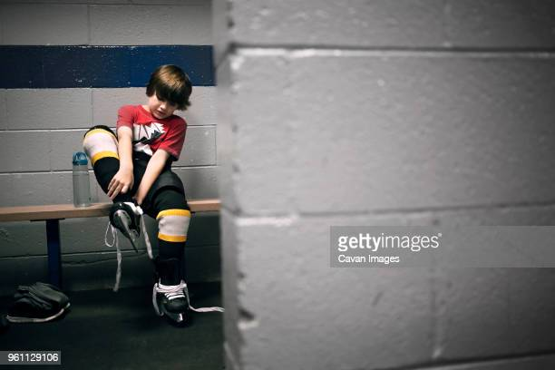 boy putting on ice hockey skates - coulisses photos et images de collection