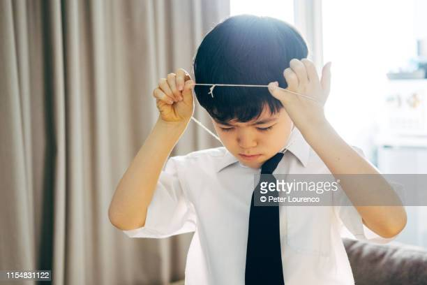 boy putting on school tie - peter lourenco stock pictures, royalty-free photos & images