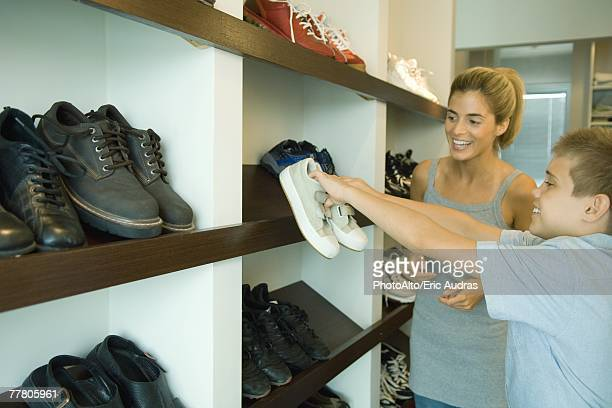 Boy putting shoes on shoe rack while mother watches