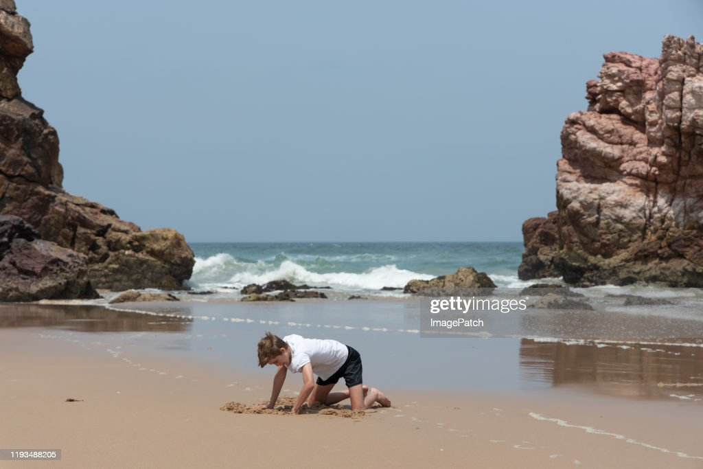Boy quietly digging in the sand at the beach : Stock Photo