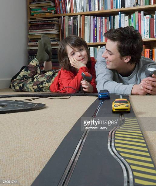 Boy (5-7) racing toy cars with man