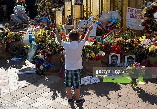 A boy raises his arms in the air in front of a memorial at the Muhammad Ali Center on June 10 2016 in Louisville Kentucky After the funeral and the...