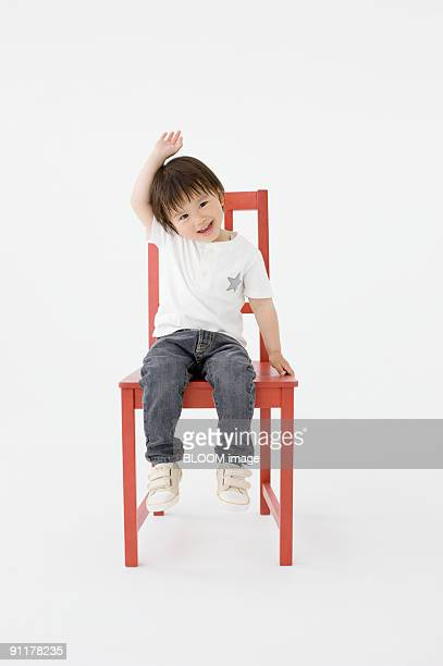 Boy raising hand sitting on chair, studio shot