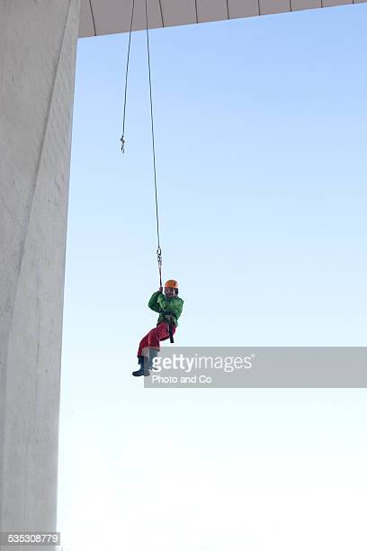 boy rappelling , acrobranching in city