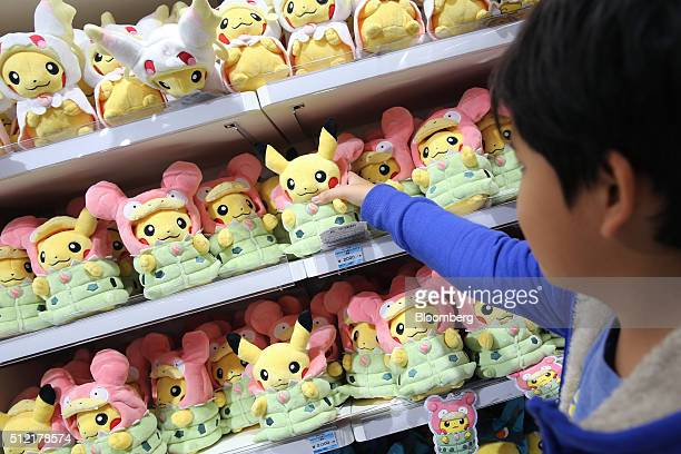 A boy reaches out for a Pikachu plush toy displayed for sale at the Pokemon Center Mega Tokyo store in Tokyo Japan on Wednesday Feb 24 2016 Pokemon a...