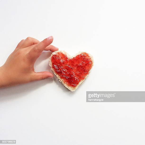 Boy reaching for heart shaped slice of bread and jam