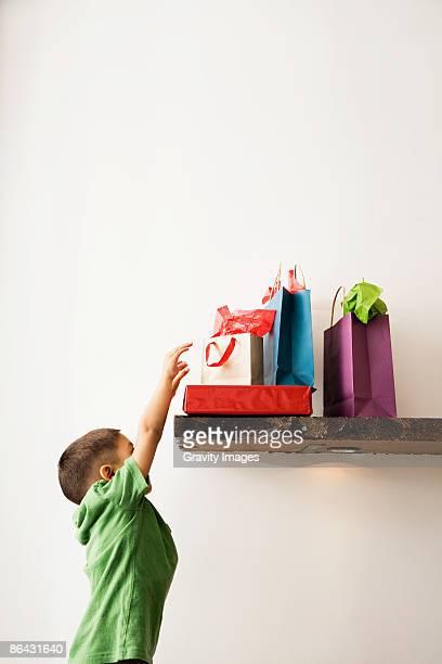 boy reaching for holiday presents on shelf - solo un bambino maschio foto e immagini stock