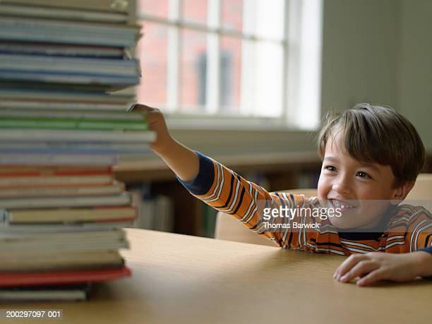 Boy (5-7) reaching for stack of books on desk, smiling