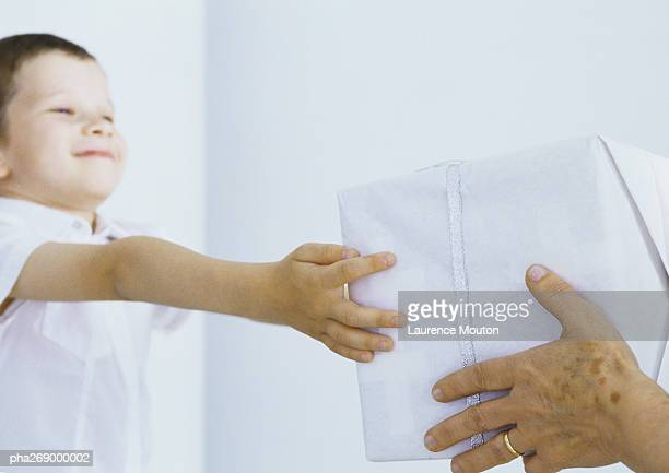 Boy reaching out receiving package