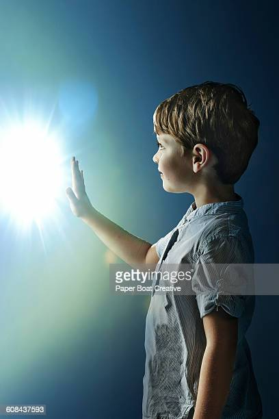 Boy reaching out to touch a glowing light