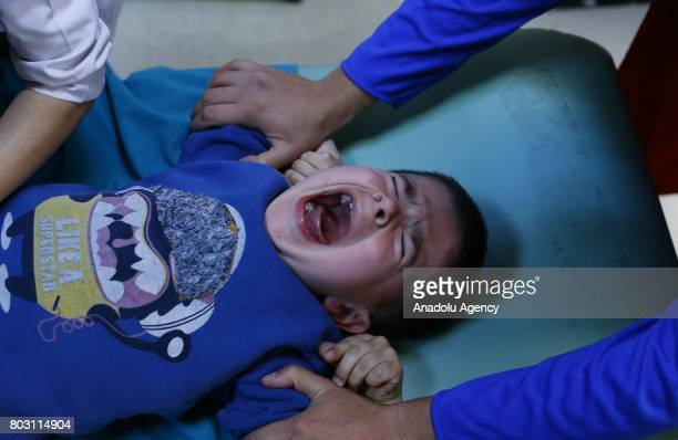 Boy reacts as paramedics perform a circumcision on him in Turkey's Ankara on June 25, 2017. Circumcision, a surgical ritual primarily based on...