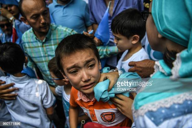 A boy reacts as Turkish plain clothes police officers try push back demonstrators during a protest of supporters of the mostly Muslim Uighur minority...