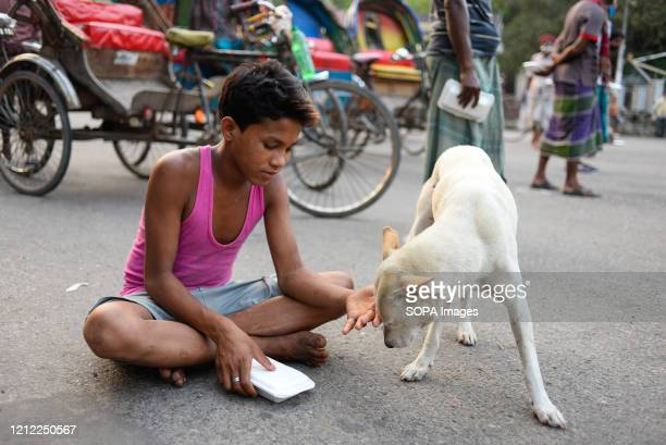 Boy reacts to a dog after receiving food on the street amid coronavirus crisis. Volunteers from Dhaka University campus donate relief food and offer...