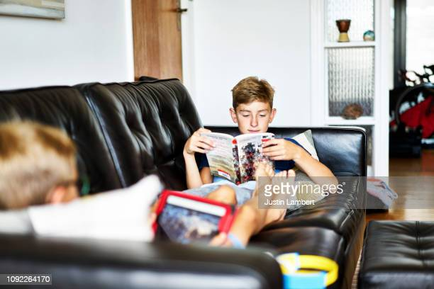 boy reading a book on the sofa with his brother sitting opposite at home - saltdean stock pictures, royalty-free photos & images