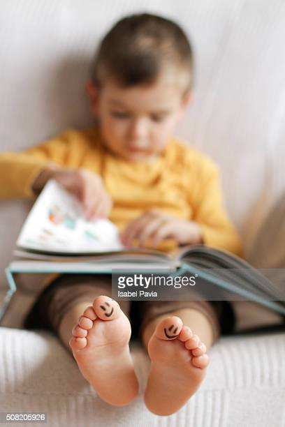 boy reading a book - male feet on face stock photos and pictures