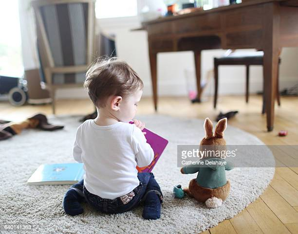 a boy reading a book to his rabbit - 1歳以上2歳未満 ストックフォトと画像