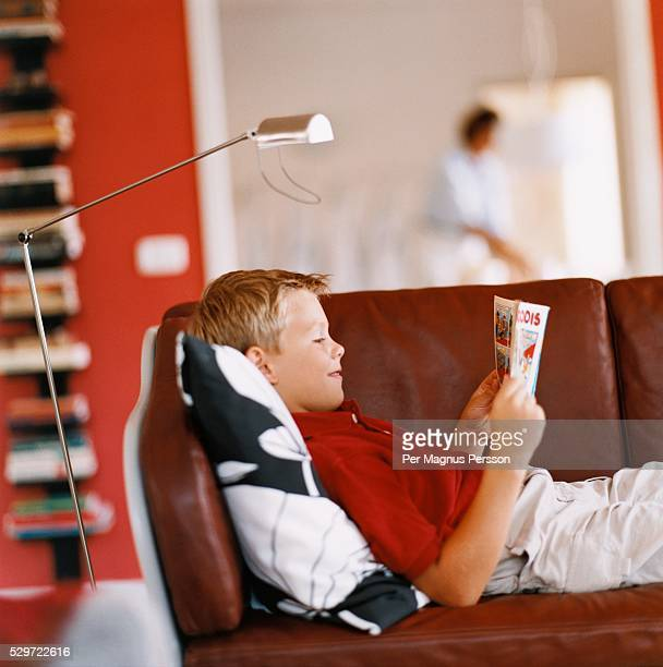 boy reading a comic book - comic book stock pictures, royalty-free photos & images