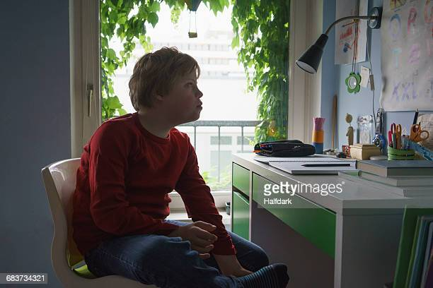 Boy reading alphabets while sitting at desk in room